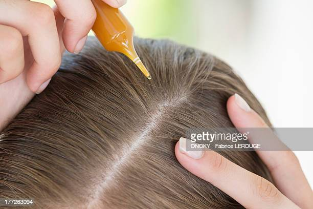 Woman pouring hair oil into her hair