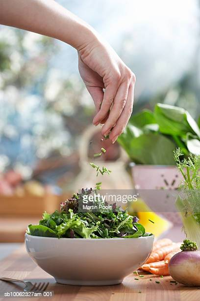 woman pouring herbs into bowl of salad in kitchen, close-up of hand - saladeira - fotografias e filmes do acervo