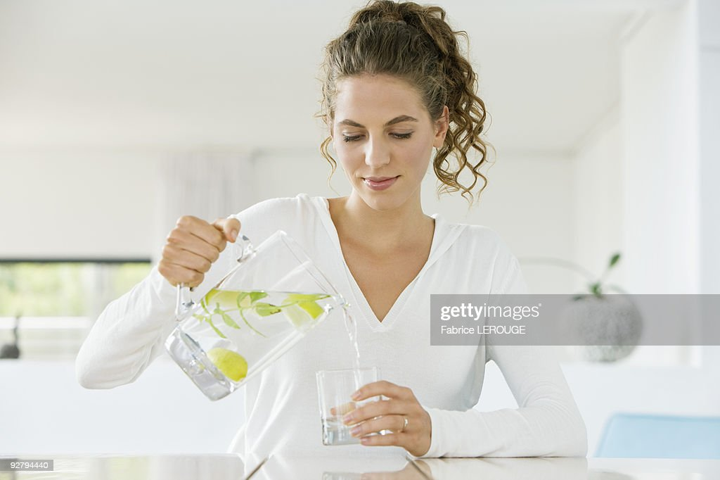 Woman pouring lemonade into a glass from a jug : Stock Photo