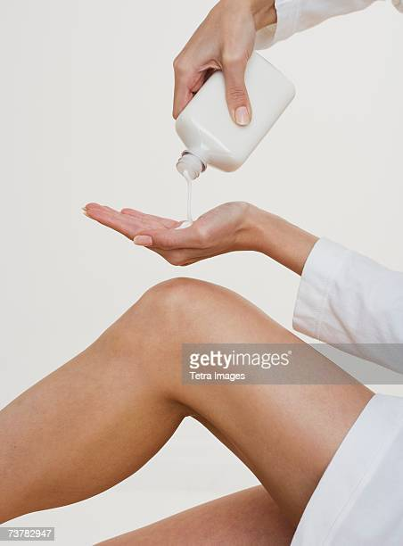 Woman pouring lotion into hand
