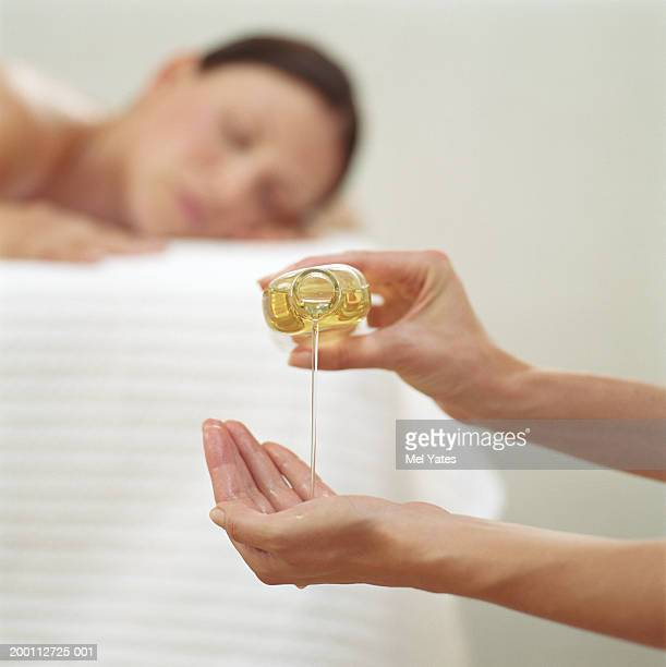 Woman pouring massage oil from bottle, focus on hand