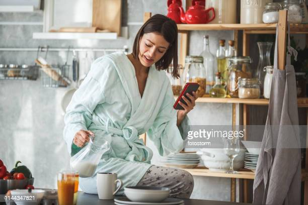 woman pouring milk into a cup and using smart phone at the kitchen counter - solo ragazze foto e immagini stock