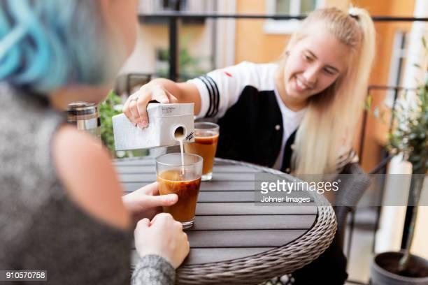 woman pouring milk into coffee - milk carton - fotografias e filmes do acervo