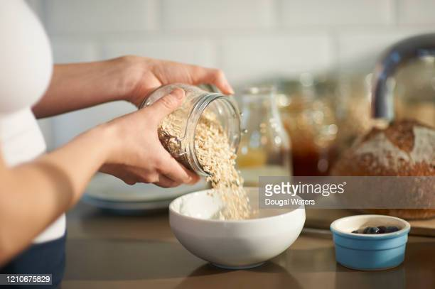 woman pouring oats into bowl in kitchen, close up. - healthy eating stock pictures, royalty-free photos & images