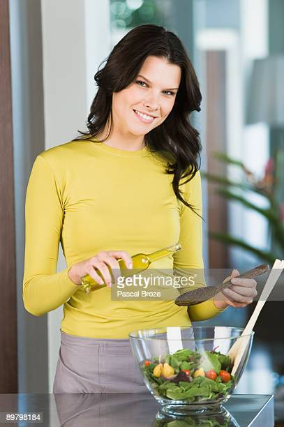 Woman pouring oil in vegetable salad