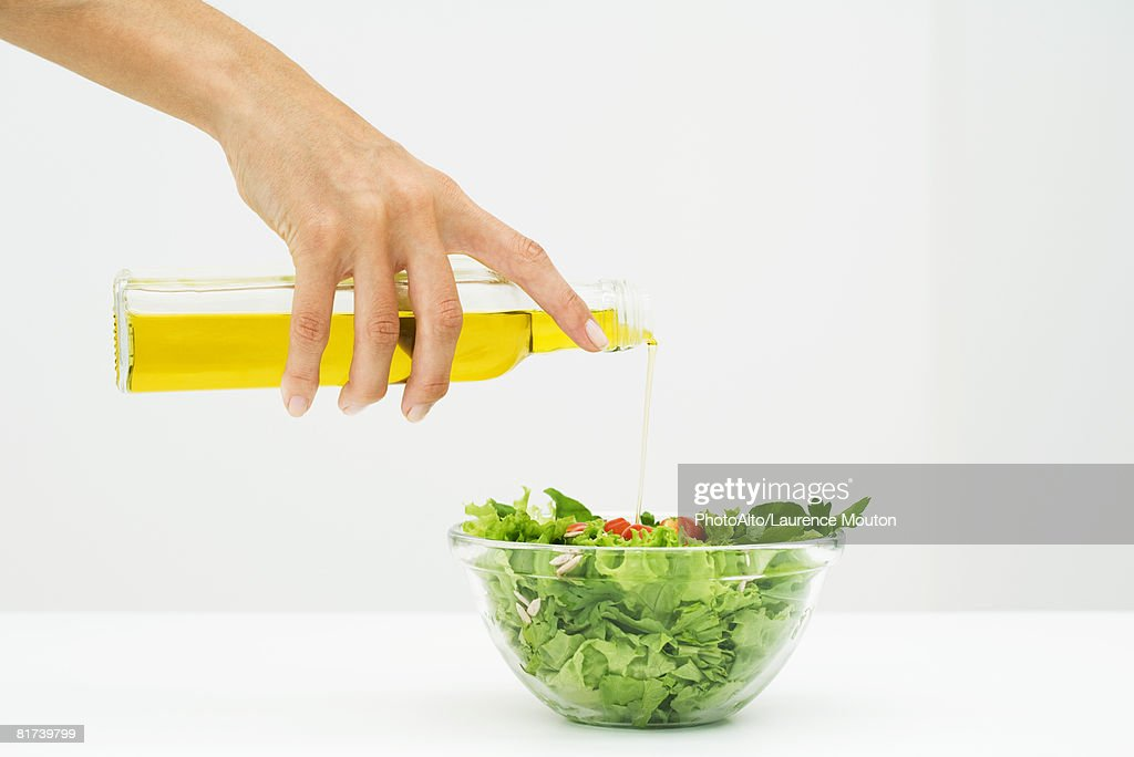 Woman pouring olive oil on salad, cropped view of hand : Stock Photo