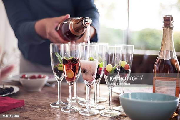 Woman pouring pink cava in champaign glasses
