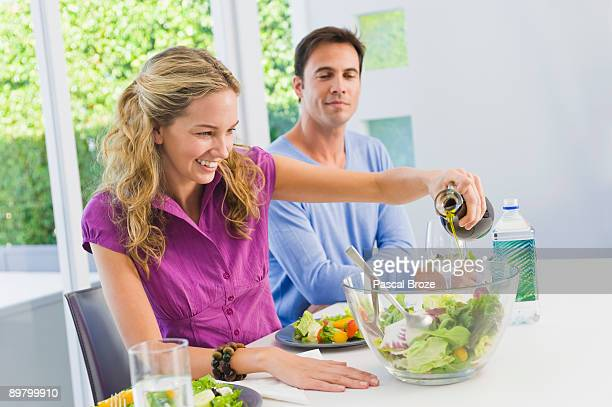 Woman pouring salad oil in salad and smiling