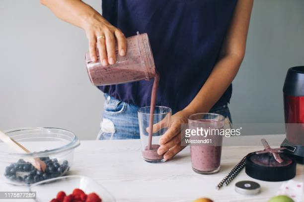 woman pouring smoothie into glasses - smoothie stock pictures, royalty-free photos & images