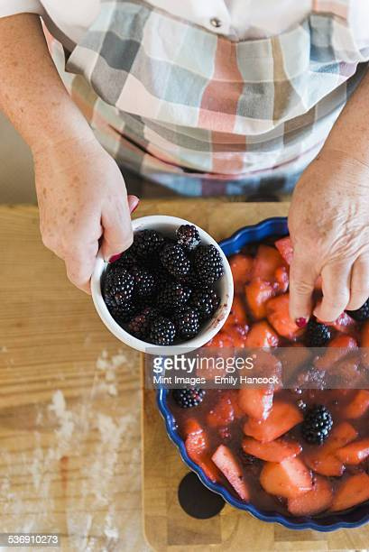 Woman pouring stewed fruit into a pie dish. Fresh blackberries.