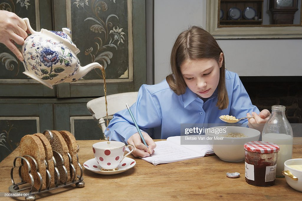 Woman pouring tea by girl (10-12) eating breakfast and writing in book : Stock Photo