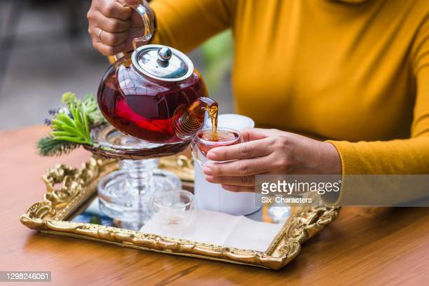 woman pouring tea from glass pot into cup, tea ceremony concept - steeping stock pictures, royalty-free photos & images