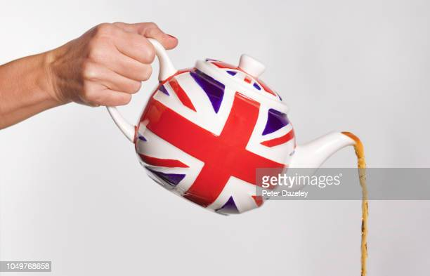 woman pouring tea from union jack teapot - cultura britânica - fotografias e filmes do acervo