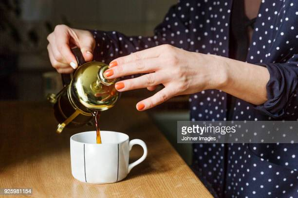 woman pouring tea into cup - preparation stock pictures, royalty-free photos & images