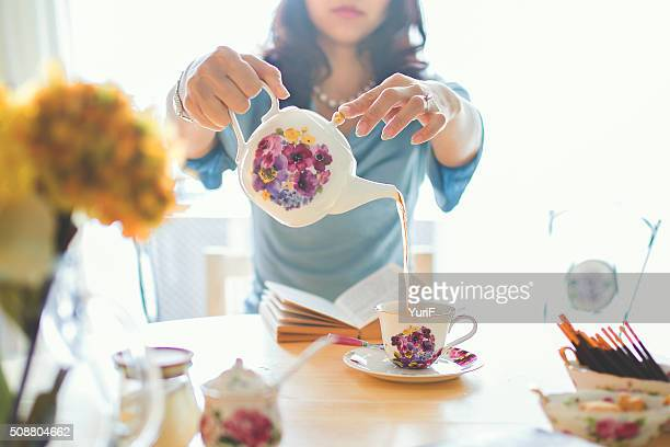 woman pouring tea. - afternoon tea stock pictures, royalty-free photos & images