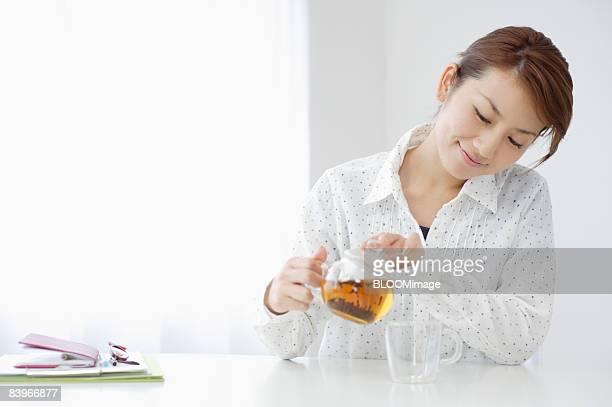 woman pouring tea - ティーポット ストックフォトと画像