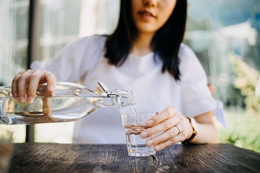 Woman pouring water from bottle into the glass at a outdoor cafe - gettyimageskorea