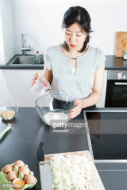 Woman pouring water in a glassbowl of flour