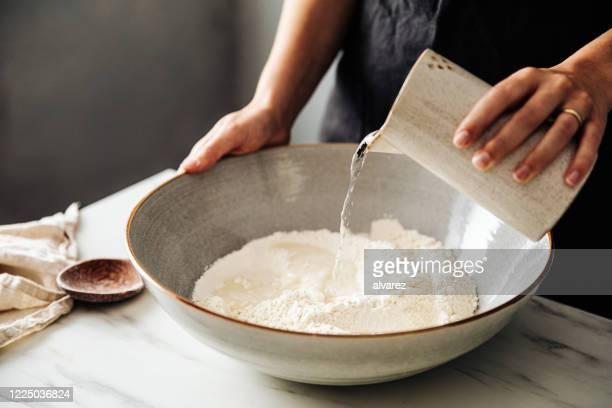 frau gießt wasser auf roggen und weizenmehl in schüssel - mehl stock-fotos und bilder