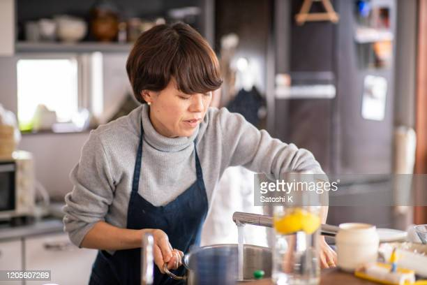 woman pouring water to cooking pot at domestic kitchen - stay at home mother stock pictures, royalty-free photos & images