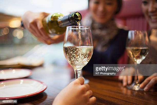 woman pouring white wine, close up - fülle stock-fotos und bilder