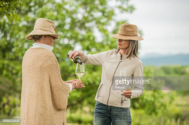 Woman pouring white wine to her friend