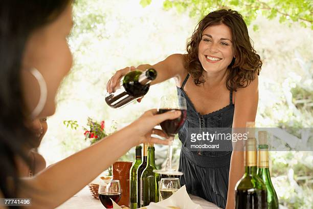 woman pouring wine at dinner party - funny customer service stock pictures, royalty-free photos & images