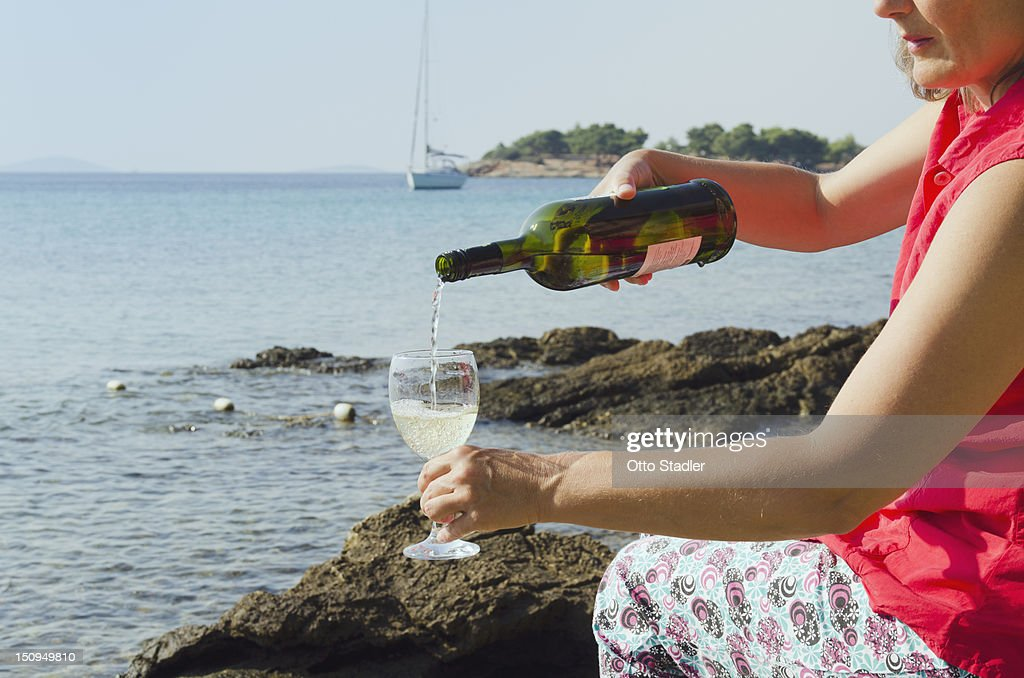 A woman pouring wine into a glass by the sea : Stock Photo