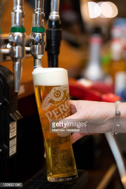 Woman pours a glass of lager in a pub on February 28, 2020 in Cardiff, Wales. A new law setting a minimum alcohol price will come into force on March...