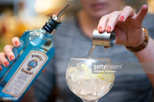 Woman pours a measure of gin into a glass on February 28, 2020 in Cardiff, Wales. A new law setting a minimum alcohol price will come into force on...