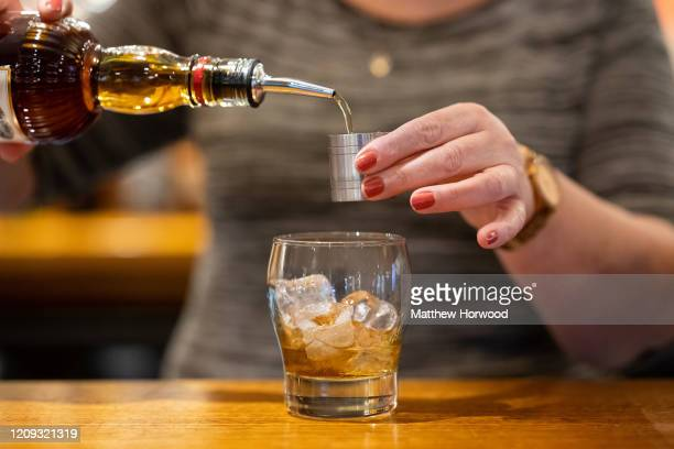 Woman pours a measure of whisky into a glass on February 28, 2020 in Cardiff, Wales. A new law setting a minimum alcohol price will come into force...