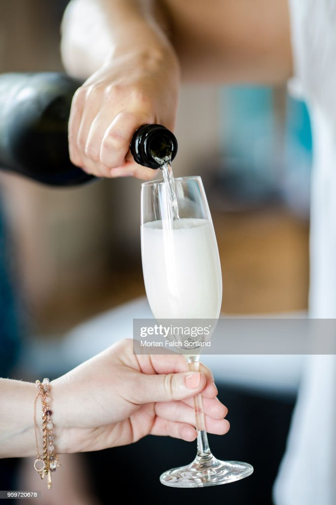 A Woman Pours Champagne into a Glass During Pre-Wedding Celebrations in Berlin, Germany Summertime : Stock-Foto