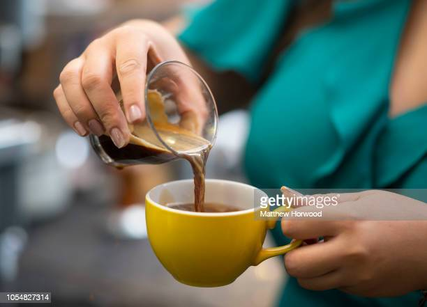 A woman pours espresso into a yellow coffee cup in a coffee shop on October 3 2018 in Cardiff United Kingdom