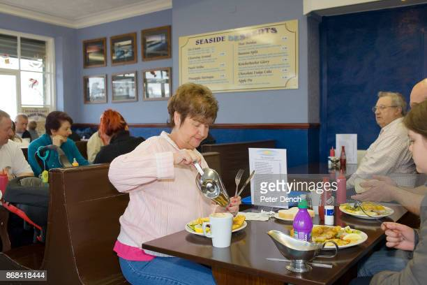 A woman pours gravy on her fish and chips served at the Seaside Cafe on Marine Promenade In 1986 world famous photographer Martin Parr published his...