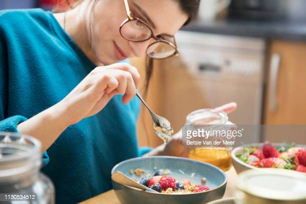 Woman pours honey over her breakfast bowl, sitting at kitchen table.