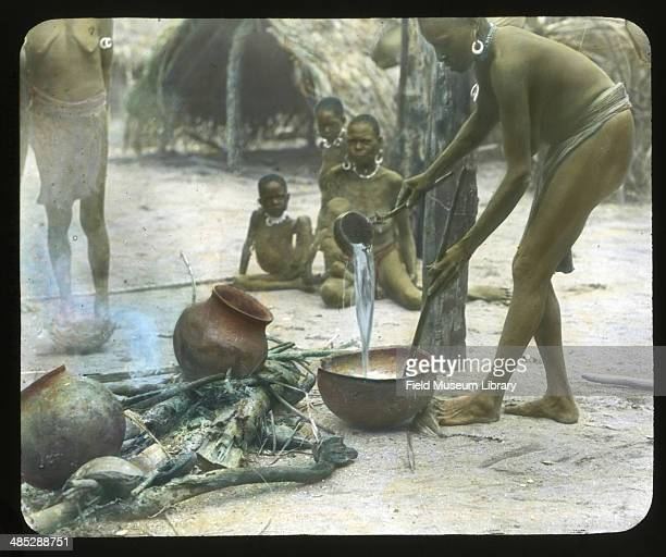 A woman pours hot water into a pot with others gathered around her Sissano Papua New Guinea November 1 1909