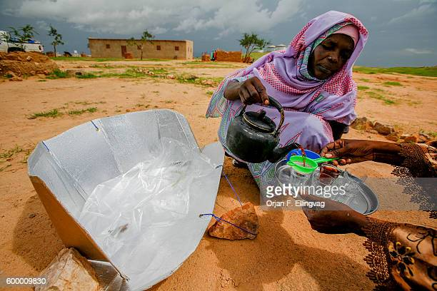 Woman pours tea in a refugee camp in Iridimi in Tchad, close to the sudanese border. The tea is boiled in a solar cooker, fabricated by women in the...