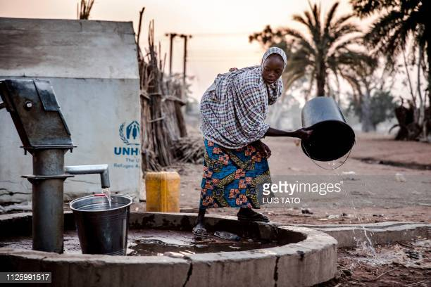 A woman pours water from a well at Malkohi refugee camp in Jimeta Adamawa State Nigeria early on February 19 four days ahead of the country's General...