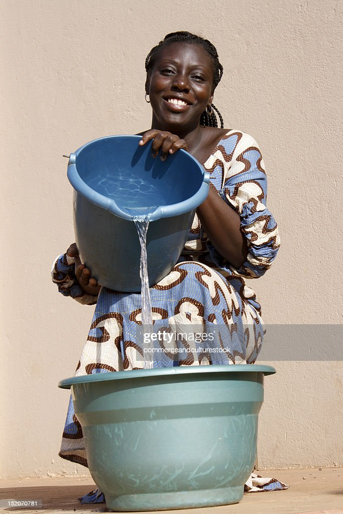 Woman pours water in bucket : Stock Photo