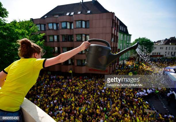 A woman pours water on fans of BVB Borussia Dortmund waiting for the arrival of their team at Borsigplatz ahead of celebrations after winning the...