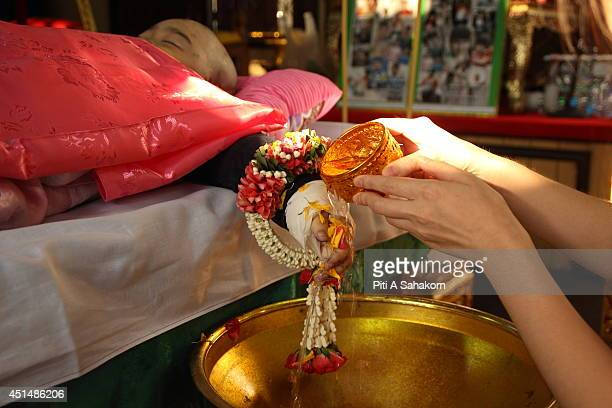 A woman pours water on the hands of the body of 6yearold Patcharakorn Yosubon the victim of a bomb blast during the last rites performed at a...
