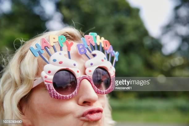 woman pouting wearing birthday eyeglasses - anniversaire humour photos et images de collection