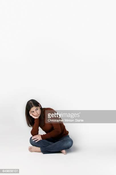 woman pouting with chin in hand - manos a la cabeza fotografías e imágenes de stock