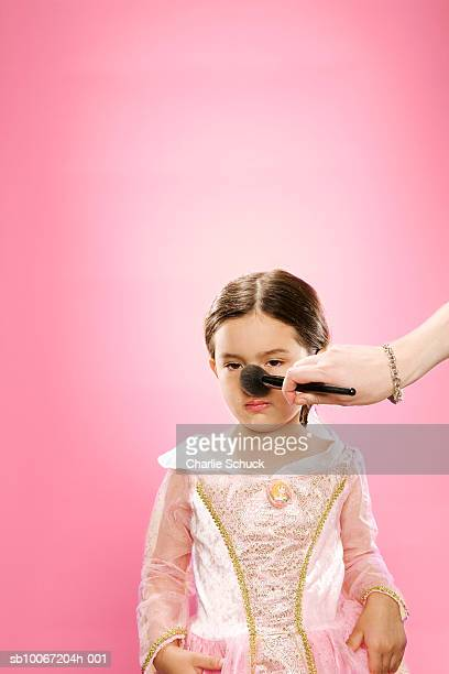 Woman powdering nose of girl (6-7) on pink background