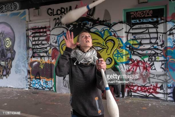 Woman practices juggling underneath a railway bridge next to the Nomadic Community Gardens, Spitalfields, London, United Kingdom.