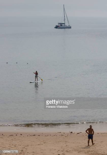 A woman practices paddle surf while a beachgoer at Praia da Duquesa takes advantage of mild autumn weather on October 25 2018 in Cascais Portugal...
