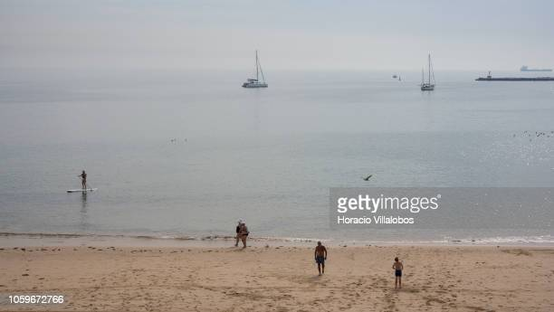 A woman practices paddle surf while beachgoers at Praia da Duquesa take advantage of mild autumn weather on October 25 2018 in Cascais Portugal...