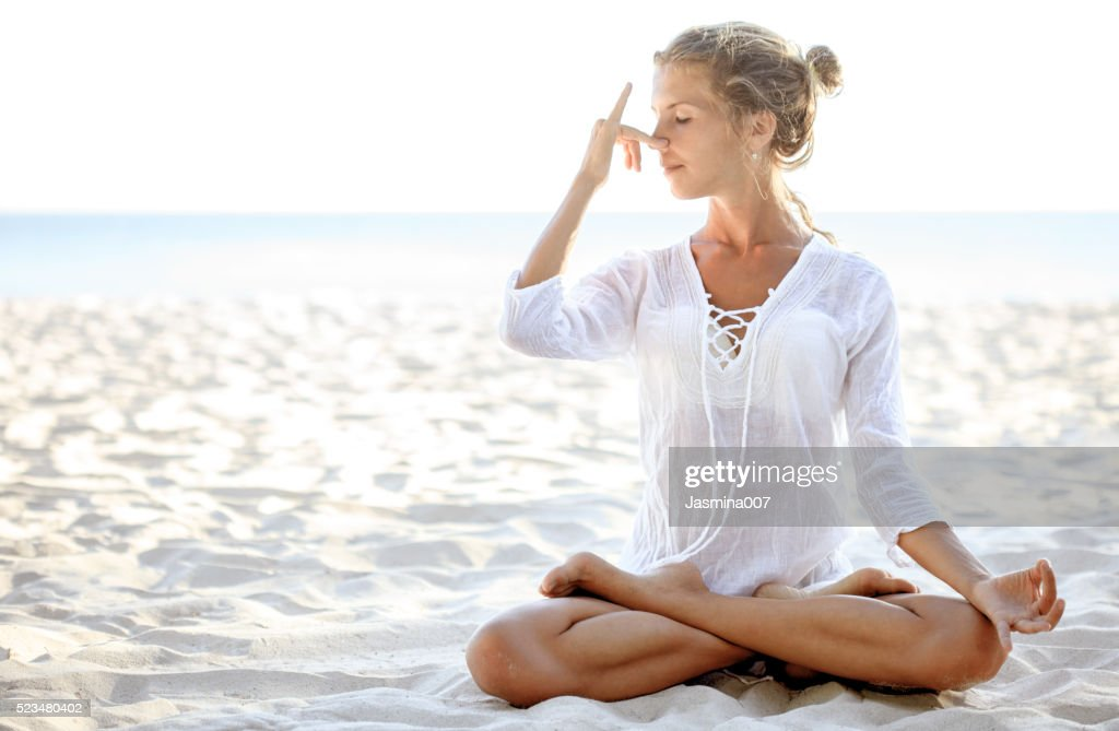 Woman practices pranayama in lotus pose on the beach : Stock Photo