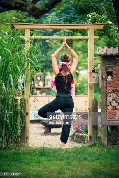 Frau praktiziert Yoga und meditiert im Garten unter einem japanischen Tor