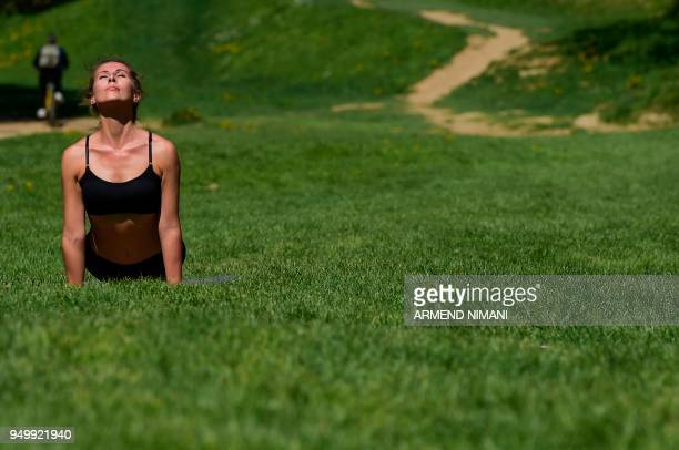 A woman practices yoga during activities marking Earth Day in Germia National Park near Pristina on April 22 2018 April 22 is observed as Earth Day...